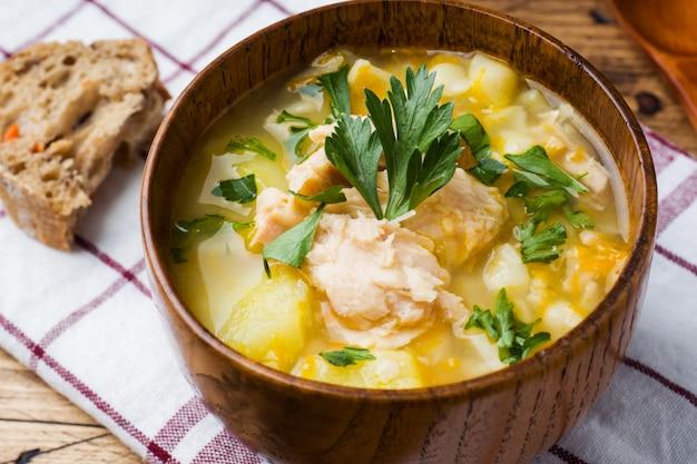 Soupe de poisson dans un bol en bois avec des herbes fraîches. Photo Premium