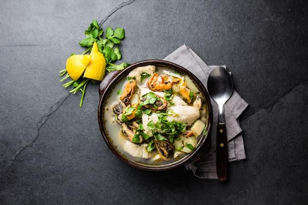 Soupe de poisson et fruits de mer dans des bols d'argile servis avec citron et coriandre. Photo Premium