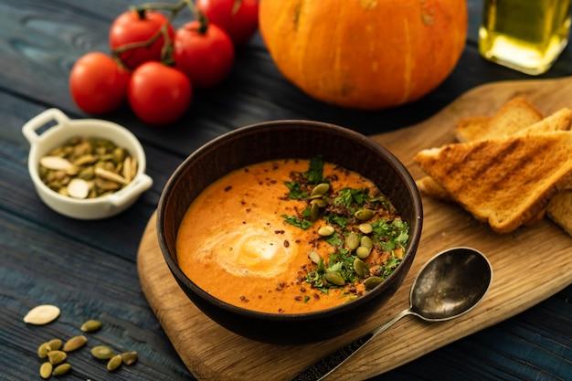 Soupe De Potiron à La Crème Sure Et Graines De Potiron Sur Une Table En Bois. Photo Premium