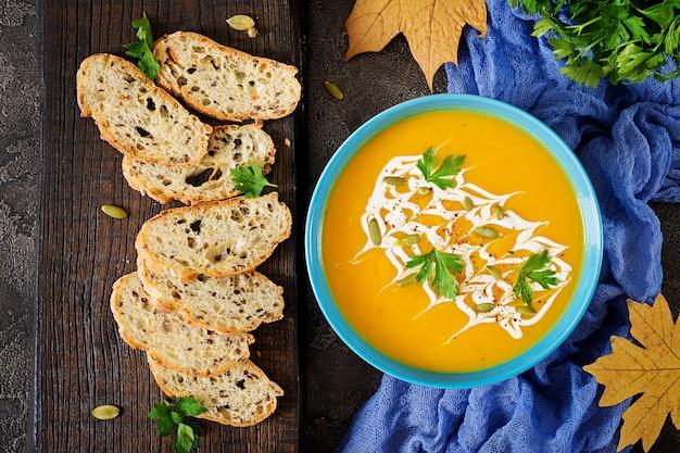 Soupe de potiron dans un bol avec du persil et des graines de citrouille. soupe végétalienne. Photo Premium