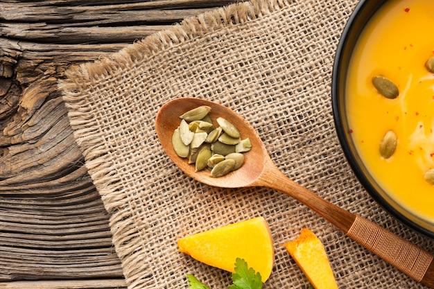Soupe De Potiron à Plat Dans Un Bol Et Une Cuillère En Bois Avec Des Graines Photo gratuit