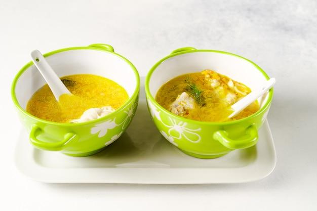 Soupe De Poulet Aux Pâtes Maison Servie Dans Des Bols Vert Clair Avec Des Cuillères En Céramique Photo Premium