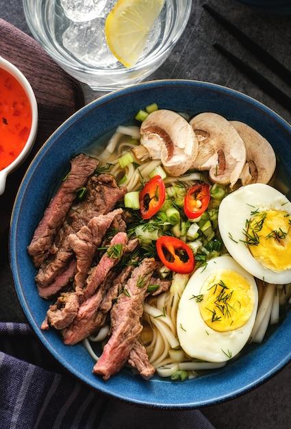 Soupe de ramen asiatique avec bœuf, œuf, ciboulette et champignons dans un bol. vue de dessus Photo Premium