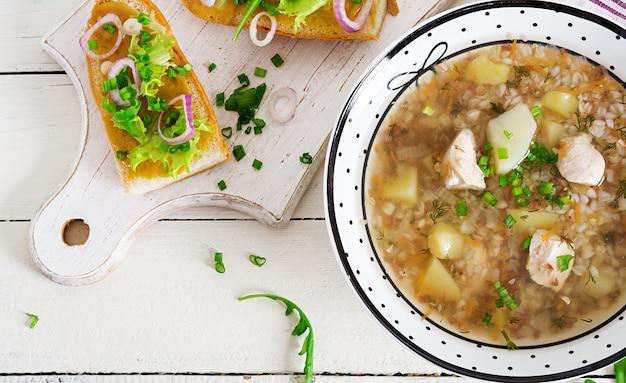Soupe de sarrasin avec du poulet dans une assiette, pain à la moutarde et un oignon rouge sur une table en bois blanche. vue de dessus Photo Premium