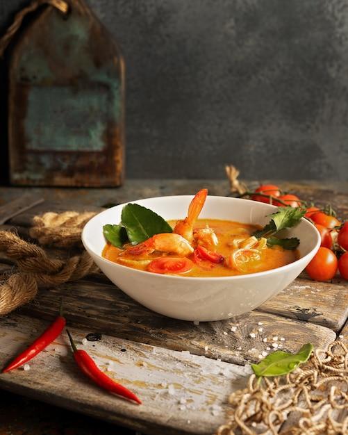 Soupe Tom Yam Aux Crevettes, Calamars Et Piments Forts Sur Une Planche De Bois Texturée. Photo Premium