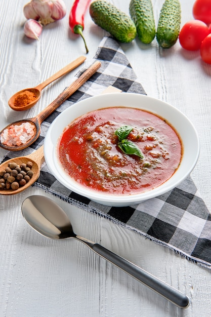 Soupe de tomates au basilic, poivre, ail et concombre sur bois Photo Premium
