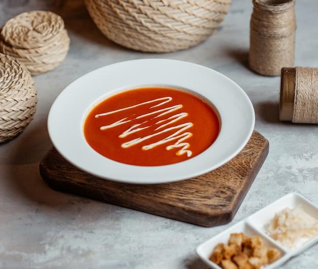 Soupe de tomates dans une assiette blanche avec une sauce à la crème. Photo gratuit