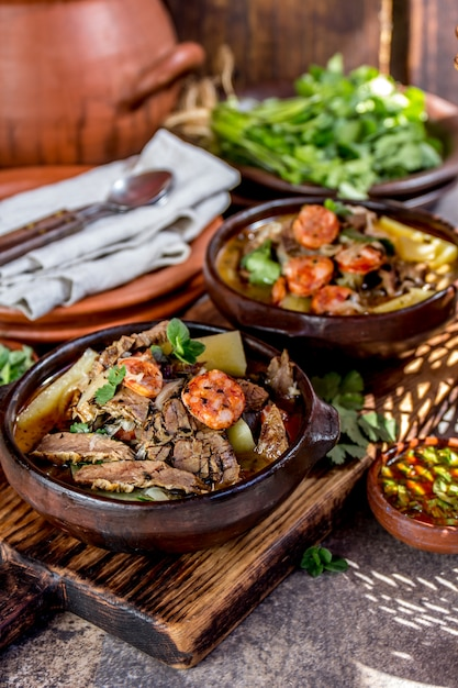 Soupe Traditionnelle Chilienne Avec Viande Grillée, Oignons Et Pommes De Terre Servis Dans Des Assiettes En Argile Photo Premium