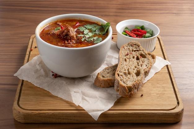 Soupe Traditionnelle Ukrainienne à Base De Betteraves, De Légumes Et De Viande Avec Du Pain Sur Une Table En Bois. Photo Premium