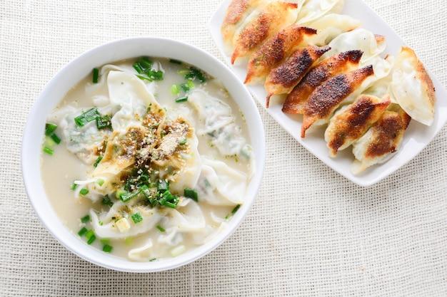 Soupe wonton aux oignons nouveaux servie dans un bol blanc, mise au point sélective Photo Premium