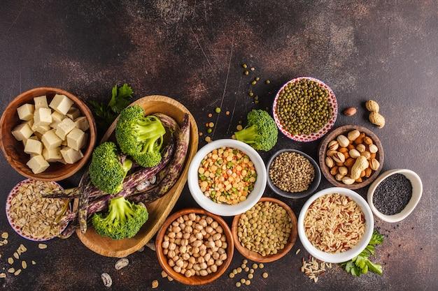 Source de protéines végétaliennes. tofu, haricots, pois chiches, noix et graines sur un fond sombre, vue de dessus, espace copie. Photo Premium