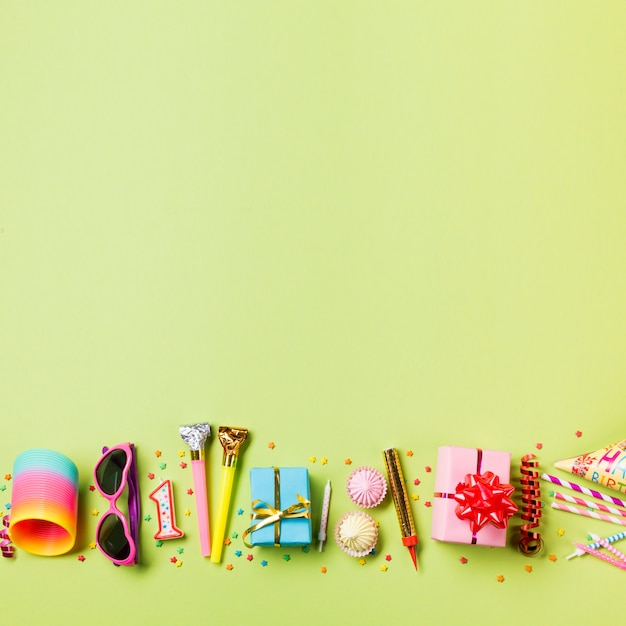 Sources colorées; des lunettes de soleil; bougie; corne de fête; boite cadeau; aalaw; banderoles et pailles sur fond vert Photo gratuit