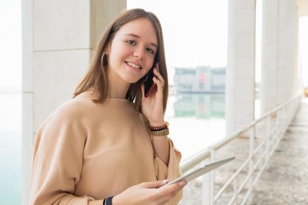 Souriant Adolescente à L'aide D'un Téléphone Et D'une Tablette à L'extérieur Photo gratuit