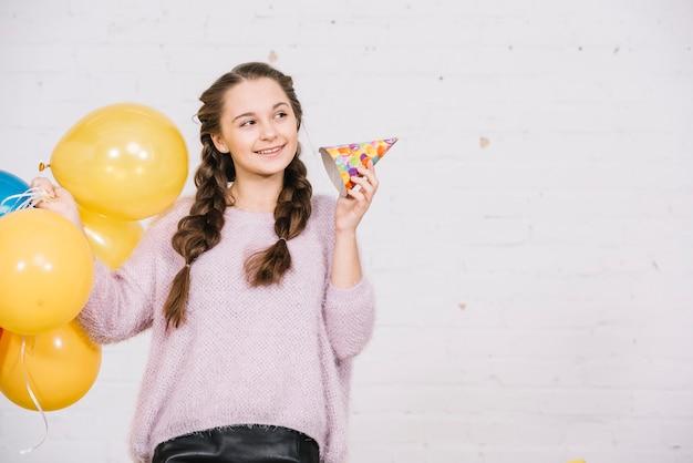 Souriant adolescente tenant des ballons et chapeau de fête à la recherche de suite Photo gratuit