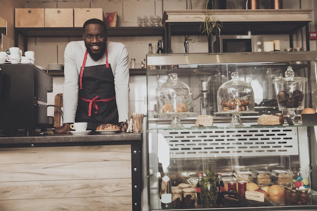 Souriant afro américain barista mâle au travail Photo Premium