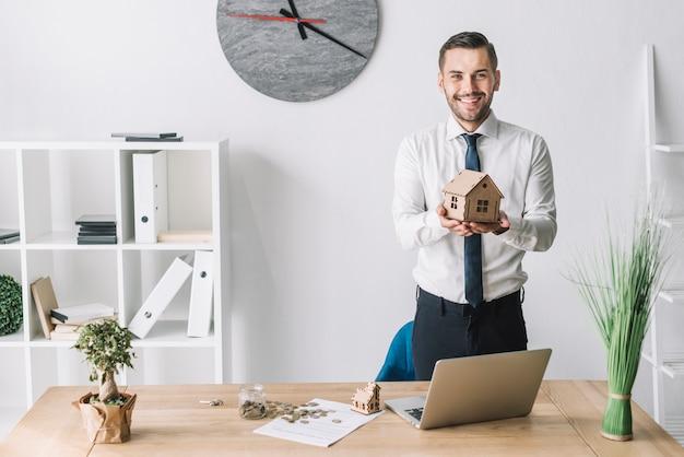 Souriant agent immobilier tenant la maison Photo gratuit