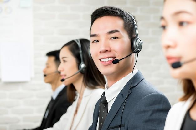 Souriant, agent de télémarketing du service clientèle asiatique en centre d'appels Photo Premium