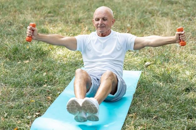 Souriant Aîné Travaillant Sur Un Tapis De Yoga Photo gratuit