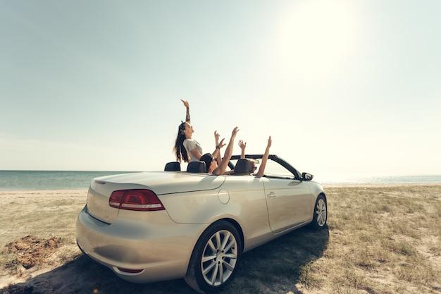 Souriant amis conduisant une voiture près de la mer et s'amusant Photo Premium