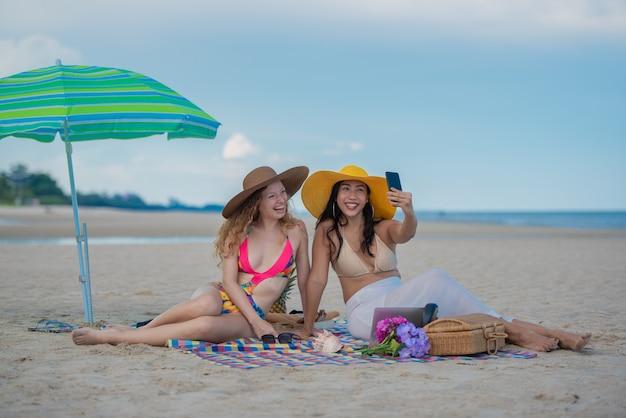 Souriant amis fille assis sur le tapis et portant chapeau prenant selfie photographier avec smartphone ensemble Photo Premium