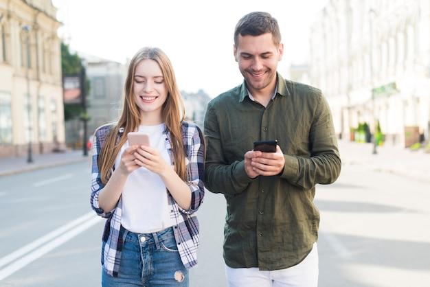 Souriant amis masculins et féminins à l'aide de téléphone portable blanc marchant ensemble dans la rue Photo gratuit
