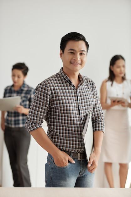 Souriant asiatique homme debout et tenant le dossier de document, avec des collègues en arrière-plan Photo gratuit