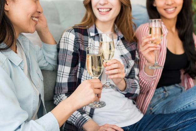 Souriant et assis sur un canapé, boire du champagne Photo gratuit