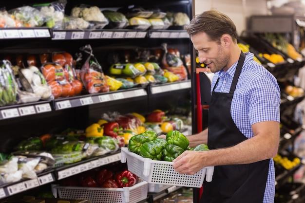 Souriant beau travailleur tenant une boîte avec des légumes Photo Premium