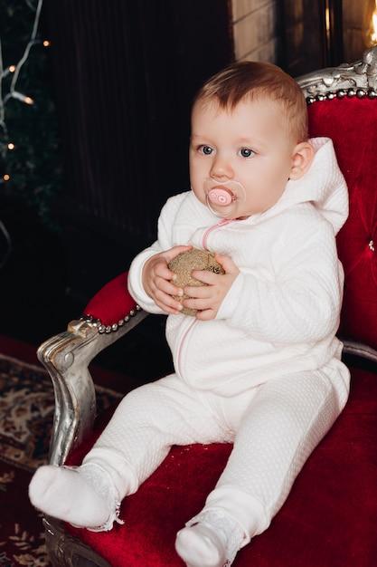 Souriant bébé fille de moins de 1 an décorer un arbre de noël dans la chambre. regardant la caméra. fête. saison des fêtes. Photo Premium