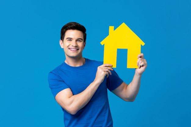 Souriant bel homme caucasien tenant la maison modèle Photo Premium