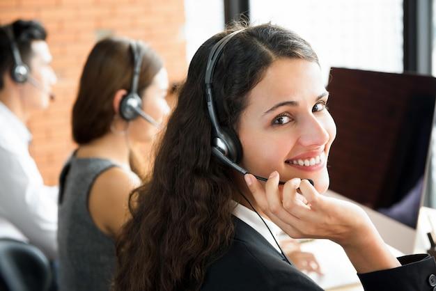 Souriant belle femme travaillant dans le centre d'appels Photo Premium