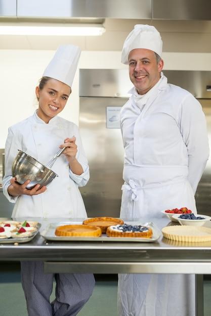 Souriant Chef Tenant Fouet Tout En étant Regardé Par Le Chef Cuisinier Photo Premium