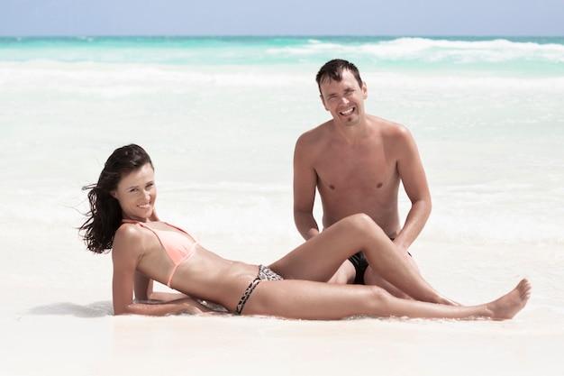 Souriant couple assis sur la plage Photo gratuit