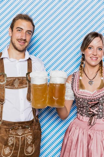 Souriant couple bavarois avec des chopes à bière Photo gratuit
