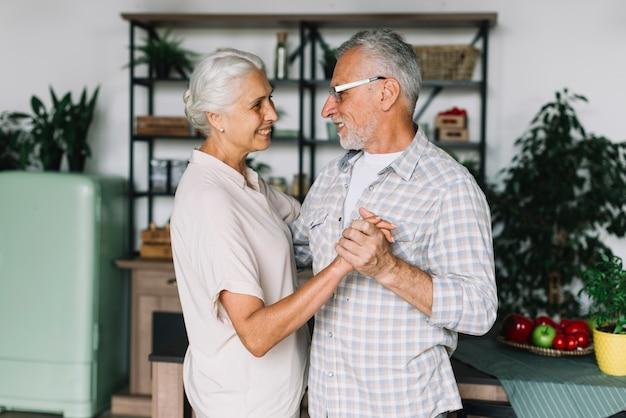 Souriant Couple De Personnes âgées Dansant Dans La Cuisine Photo gratuit