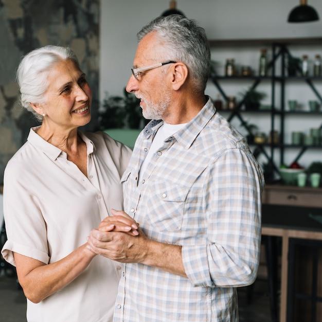 Souriant Couple De Personnes âgées Dansant Ensemble Dans La Cuisine Photo gratuit
