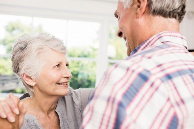 Souriant couple de personnes âgées danser à la maison Photo Premium