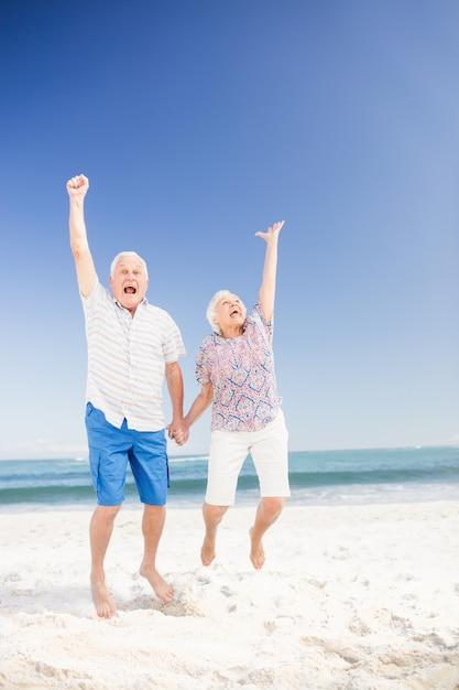 Souriant couple de personnes âgées sautant Photo Premium