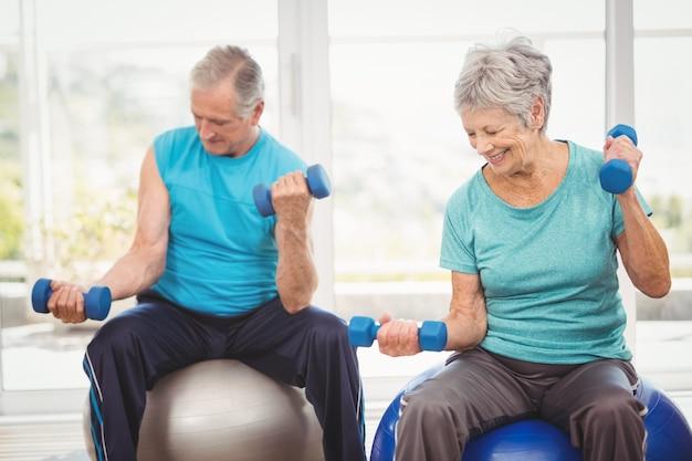 Souriant couple de personnes âgées tenant des haltères pendant l'exercice Photo Premium