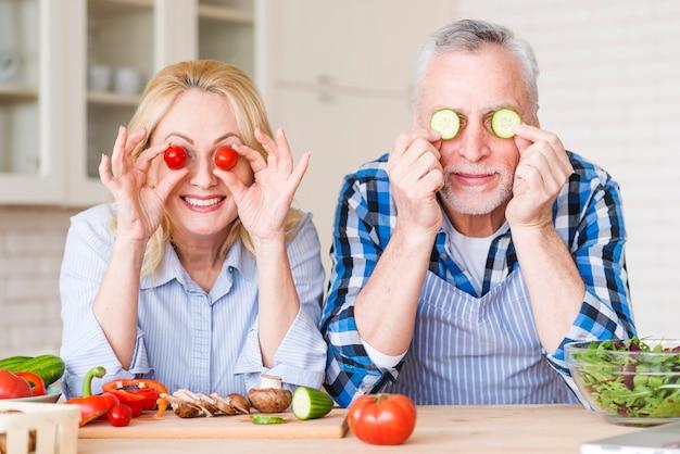 Souriant Couple De Personnes âgées Tenant Des Tomates Cerises Et Des Tranches De Concombre Devant Leurs Yeux Photo gratuit