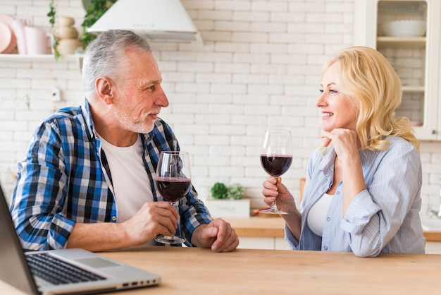 Souriant Couple De Personnes âgées Tenant Un Verre De Vin Rouge à La Main Se Regardant Avec Un Ordinateur Portable Sur La Table Photo gratuit