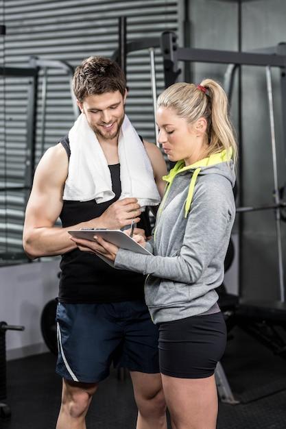 Souriant couple prenant des notes au gymnase de crossfit Photo Premium
