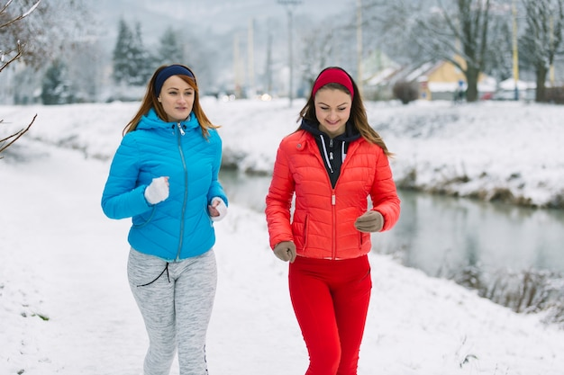 Souriant deux amies jogging en saison d'hiver Photo gratuit