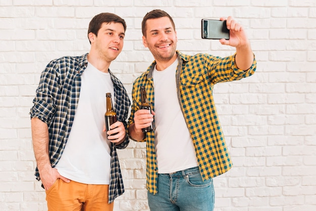 Souriant deux amis de sexe masculin tenant une bouteille de bière prenant selfie sur téléphone mobile Photo gratuit