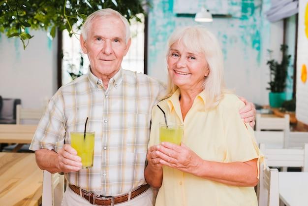 Souriant Embrassant Couple De Personnes âgées Tenant Des Verres De Jus Photo gratuit