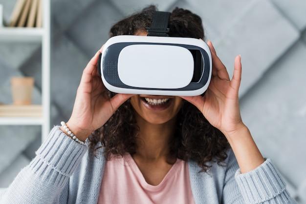 Souriant employé ethnique femme utilisant des lunettes de réalité virtuelle Photo gratuit