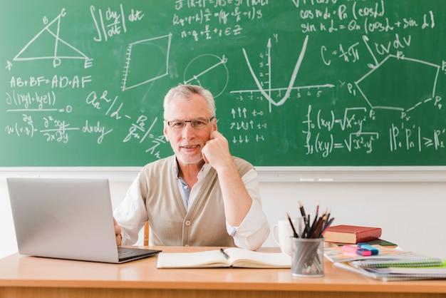 Souriant enseignant près d'un ordinateur portable dans la salle de lecture Photo gratuit