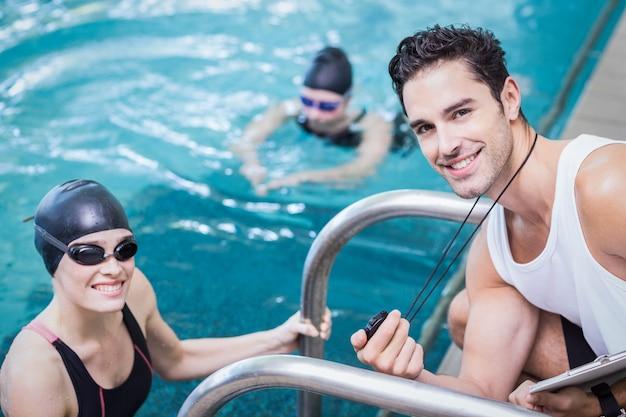 Souriant entraîneur montrant le chronomètre chez le nageur au centre de loisirs Photo Premium
