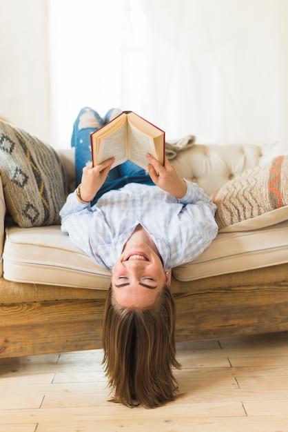 Souriant à l'envers femme tenant un livre relié Photo gratuit