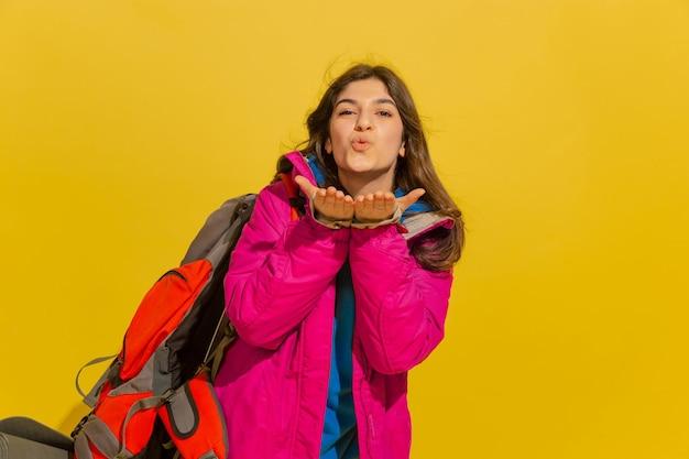 Souriant, Envoyant Un Baiser. Portrait D'une Jeune Fille De Touriste Caucasienne Joyeuse Avec Sac Et Jumelles Isolé Sur Fond De Studio Jaune. Photo gratuit